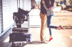 a man and a woman in a long distance relationship have a last hug before saying goodbye at the airport